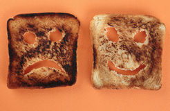 Happy and sad toast on acutting board Royalty Free Stock Images