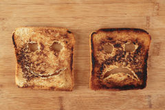 Happy and sad toast on a cutting board Royalty Free Stock Image