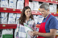 Happy Salesman Assisting Customer In Buying Pet Food Royalty Free Stock Image