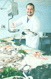 Happy salesman in black glove holding fish Stock Images