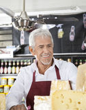 Happy Salesman In Cheese Shop Stock Images