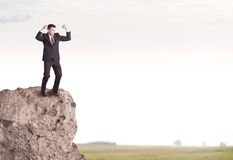 Happy salesman on cliff in the country Stock Images