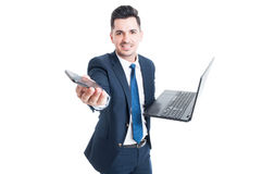 Happy salesman holding laptop and smartphone as multitasking con Royalty Free Stock Image