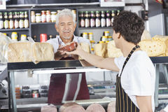 Happy Salesman Receiving Cheese From Colleague In Grocery Shop Royalty Free Stock Images