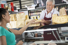 Happy Salesman Selling Cheese To Female Customer. At grocery shop Stock Photography