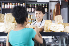 Happy Salesman Selling Cheese To Female Customer. Happy young salesman selling cheese to female customer at grocery shop Stock Images