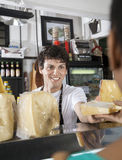 Happy Salesman Selling Cheese To Female Customer. Happy young salesman selling cheese to female customer at grocery store Royalty Free Stock Photography