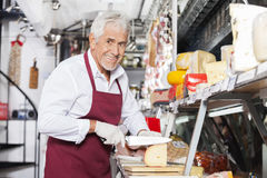 Happy Salesman Slicing Cheese In Shop. Portrait of happy salesman slicing cheese at counter in shop Royalty Free Stock Photos