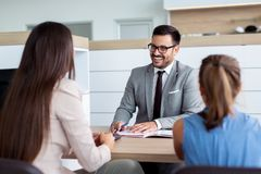 Happy salesman talking about potential deals with customers. Happy young salesman talking about potential deals with customers stock images
