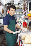 Happy Salesman Weighting Cheese On Weight Scale royalty free stock photos