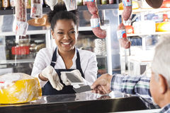 Happy Saleswoman Accepting Mobile Payment From Customer. In cheese shop stock photo