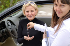 Happy saleswoman handing over car keys Stock Images