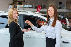 Happy saleswoman handing over car keys to the attractive young female owner. Of new white car Royalty Free Stock Photos