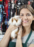 Happy Saleswoman Holding Cute Guinea Pig At Store Royalty Free Stock Image