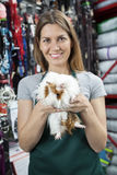Happy Saleswoman Holding Guinea Pig At Store Royalty Free Stock Photography