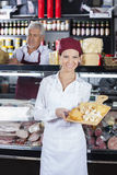 Happy Saleswoman Holding Various Cheese On Board In Store. Portrait of happy young saleswoman holding various cheese on cutting board with colleague in Stock Photos