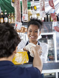 Happy Saleswoman Selling Cheese To Customer At Shop Stock Image