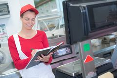 Happy saleswoman weighing meat at supermarket. Happy saleswoman weighing meat at the supermarket stock image