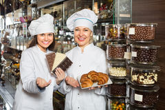 Happy saleswomen with chocolates Stock Photography