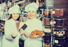 Happy saleswomen with chocolates Royalty Free Stock Images