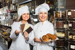 Happy saleswomen with chocolates. Smiling saleswomen offering  delicious chocolate and confectionery. Selective focus Stock Image