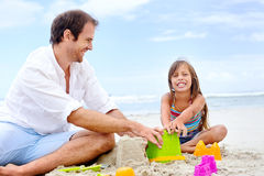Happy sand castle child. Happy healthy family father and daughter building sand castle on the beach smiling and carefree royalty free stock photo