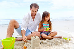 Happy sand castle child. Happy healthy family father and daughter building sand castle on the beach smiling and carefree stock images