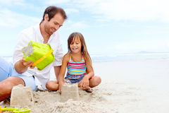 Happy sand castle child. Happy healthy family father and daughter building sand castle on the beach smiling and carefree royalty free stock image