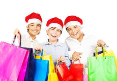 Happy Santa boys with gifts. Kids carrying colorful shopping bags with Christmas presents isolated over white background, smiling preteen friends in red hats Stock Photo