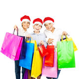 Happy Santa boys with gifts. Kids carrying colorful shopping bags with Christmas presents isolated over white background, smiling preteen friends in red hats Stock Photography