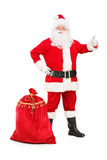 Happy Santa Claus with a bag giving a thumb up. Full length portrait of a happy Santa Claus with a bag giving a thumb up on white background Royalty Free Stock Image