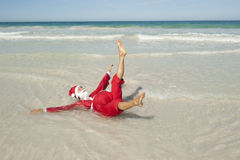 Happy Santa Claus Beach Holiday. Santa Claus happy lying in shallow water at beach, having fun and joy off duty at tropical holiday vacation, with ocean and blue stock images