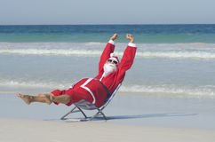 Happy Santa Claus at Beach Holiday. Santa Claus happy relaxed sitting with hands up at beach, having fun and joy off duty at tropical holiday vacation, with royalty free stock photography