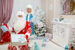Happy Santa Claus and beautiful granddaughter with New Year`s gifts in hands in festive interior. New Year`s and Royalty Free Stock Image