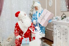 Happy Santa Claus and beautiful granddaughter are sitting indoors in the New Year`s interior and holding New Year`s Stock Photos
