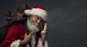 Santa Claus on the phone. Happy Santa Claus carrying an heavy sack with Christmas gifts and answering phone calls royalty free stock images