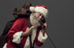 Santa Claus on the phone. Happy Santa Claus carrying an heavy sack with Christmas gifts and answering phone calls royalty free stock photo