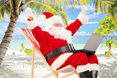 Happy Santa Claus on a chair working on a laptop and gesturing h. Appiness, on a tropical beach Royalty Free Stock Image