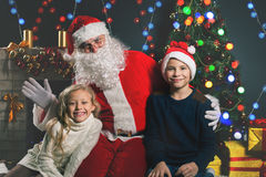 Happy Santa Claus and children around the decorated Christmas tree Stock Photos