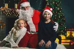 Happy Santa Claus and children around the decorated Christmas tree. Image of happy Santa Claus and children around the decorated Christmas tree Royalty Free Stock Photo