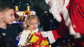 Happy Santa Claus and children around the decorated Christmas tree stock video footage