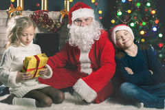 Happy Santa Claus and children around the decorated Christmas tree Royalty Free Stock Photo