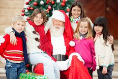 Happy Santa Claus And Children. Portrait of happy Santa Claus and children outside house Royalty Free Stock Photography