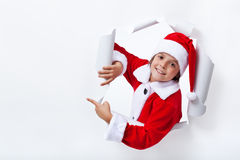 Happy Santa Claus costume boy pointing to copy space. Christmas advertising Stock Photos