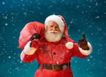 Happy Santa Claus gesturing thumb up with big bag full of gifts to children. Royalty Free Stock Photography
