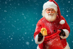 Happy Santa Claus with gift on blue background. Merry Christmas & New Year's Eve concept Royalty Free Stock Photos