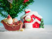 Happy Santa Claus with gifts box on the snow sled going to house. near house have Snowman and Christmas Tree. Santa Claus. And house on the snow. Christmas and Royalty Free Stock Image
