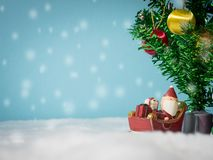Happy Santa Claus with gifts box on the snow sled going to house. near house have Snowman and Christmas Tree. Santa Claus. And house on the snow. Christmas and Stock Photography