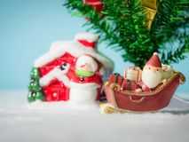 Happy Santa Claus with gifts box on the snow sled going to house. near house have Snowman and Christmas Tree. Santa Claus. And house on the snow. Christmas and Stock Photo