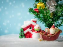 Happy Santa Claus with gifts box on the snow sled going to house. near house have Snowman and Christmas Tree. Santa Claus. And house on the snow. Christmas and Stock Images